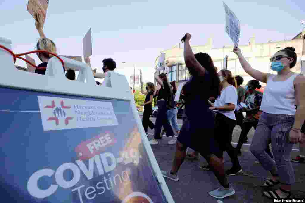 Marchers walk past a sign advertising testing for the coronavirus disease (COVID-19) during a Juneteenth Awareness Walk to demonstrate against racial inequality in the aftermath of the death in Minneapolis police custody of George Floyd, in Boston, Massachusetts, U.S., June 18, 2020.