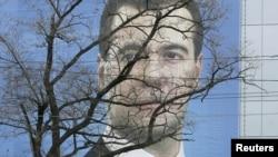 Пешеходы проходят портрета президента России Дмитрия Медведева в Ростове-на-Дону, 20 ноября 2011 года.