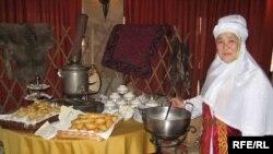 """Женщина в национальной одежде предлагает клиентам ресторана суп """"Наурыз"""". Алматы, 22 марта 2009 года."""