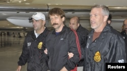 "The Russian report says that the case of jailed Russian arms dealer Viktor Bout (center) shows U.S. ""double standards"" when it comes to human rights."