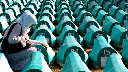 A Bosnian Muslim woman mourns over a casket at the Potocari Memorial Center  during the 2008 burial of 308 Bosnian Muslims killed by Bosnian Serb forces in Srebrenica.