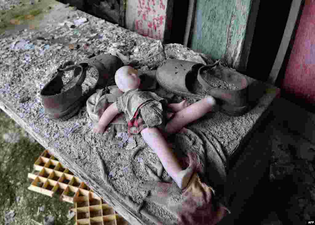 "A doll and shoes lay on a bench in a nursery school in the ""ghost town"" of Pripyat near the Chernobyl nuclear power plant on April 24. April 26 marks the 30th anniversary of the disaster. (AFP/Genya Savilov)"