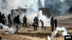 Түркиядан Сирия тарапка өтүүнү көздөгөн күрттөр коопсуздук күчтөрү менен кагылышууда. 22-сентябрь, 2014-жыл.