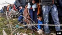 A boy looks on as he waits in line for permission to cross the border between Greece and Macedonia after Macedonia started granting passage only to refugees from Syria, Iraq, and Afghanistan last month.