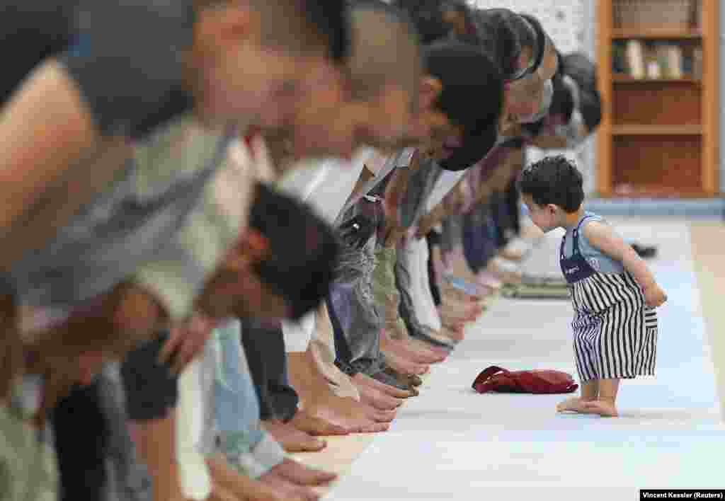 A child walks near people attending midday prayers at Strasbourg Grand Mosque in Strasbourg, France on the first day of Ramadan. (Reuters/Vincent Kessler)