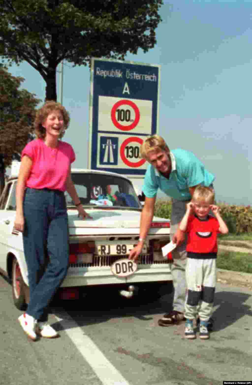 A family removes their DDR (Deutsche Demokratische Republik) badge after crossing intoKlingenbach, Austria.