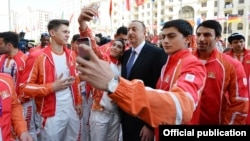 Azerbaijani President Ilham Aliyev poses for a few selfies as he meets with European Games athletes in Baku.
