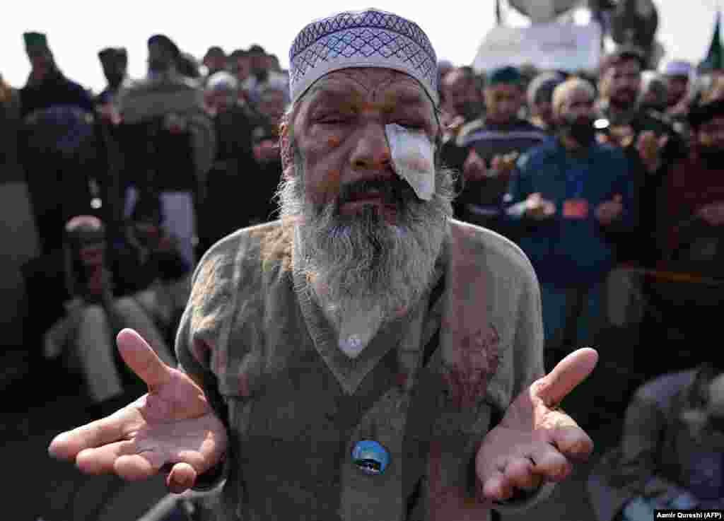 An injured elderly Pakistani protester of the Tehreek-e Labaik Yah Rasool Allah Pakistan religious group prays along with others after their leader announced the end of a sit-in protest on a blocked flyover bridge in Islamabad on November 27. (Reuters/Vasily Fedosenko)