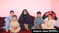 A Afghan women with her family in Herat Province after they are deported from Iran (file photo)