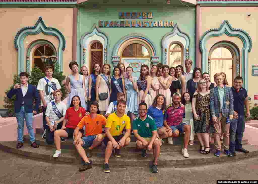The group pose with a group of unwitting Russian high-school students on their graduation day.