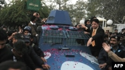 Police escort an armored vehicle carrying arrested bodyguard Malik Mumtaz Hussain Qadri, the alleged killer of Punjab Governor Salman Taseer in Rawalpindi on January 6.