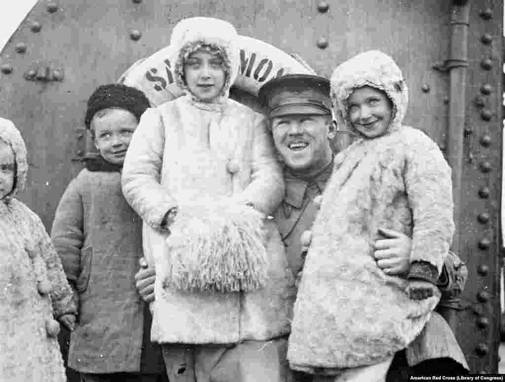A soldier from Chicago with a group of children fleeing Russia on a Red Cross boat.