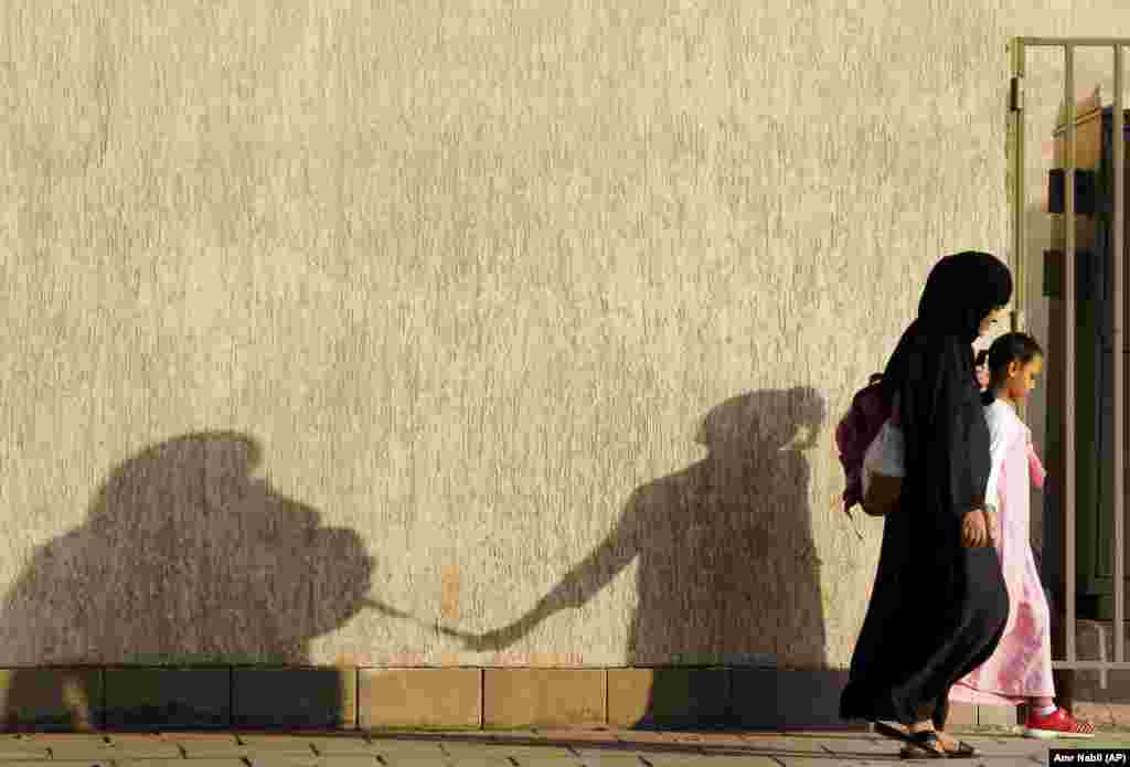 The shadows of a mother and her daughter are reflected on a wall as they walk to school in Jeddah, Saudi Arabia. (AP/Amr Nabil)