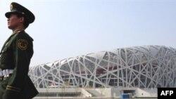 Kineski policajac ispred Nacionalnog olimpijskog stadiona