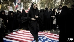 A woman steps on a U.S. flag outside the former U.S. embassy in Tehran.