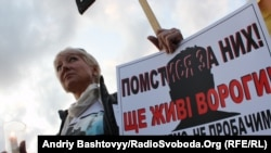 A mourner for slain journalist Heorhiy Gongadze in Kyiv on September 16 questions official efforts to identify the mastermind of the killing.