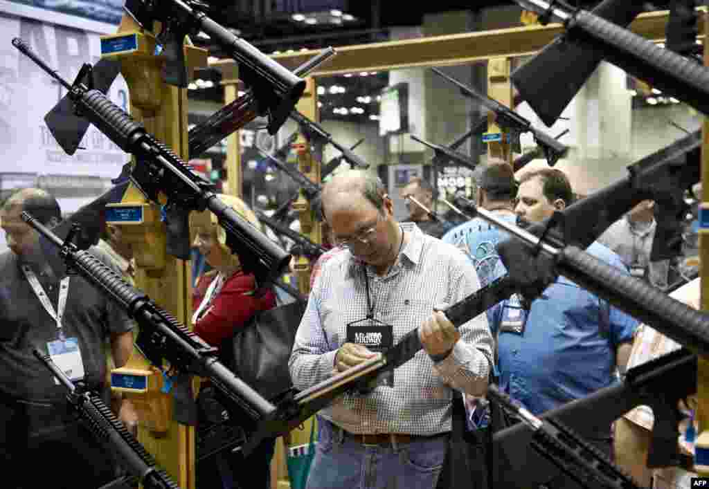 A convention goer inspects a rife in the exhibition hall at the 143rd National Rife Association (NRA) Annual Meetings and Exhibits at the Indiana Convention Center in Indianapolis, Indiana. (AFP/Karen Bleier)