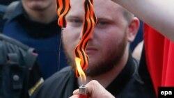 Украінскія нацыяналісты спальваюць георгіеўскія стужачкі падчас сьвяткаваньня Дня Перамогі ў Кіеве, 2016 год
