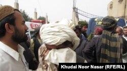 Familjarët e pikëlluar të të vrarëve para njhë spitali civil