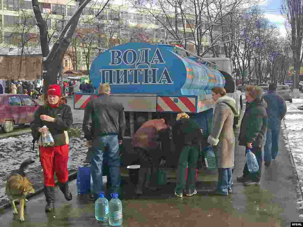 Residents of the Kurenivka district of Kyiv line up for drinking water.