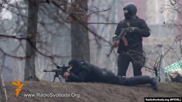 A still photo from RFE/RL Ukrainian Service video (below) showing Ukrainian security forces with a Kalashnikov assault rifle and sniper rifle, respectively, in a confrontation with protesters in Kyiv on February 20, when dozens of Euromaidan supporters were gunned down.