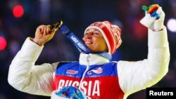 Russian gold medalist Aleksandr Legkov celebrates as he receives his medal for the men's cross-country 50-kilometer mass start race during the closing ceremony for the Sochi 2014 Winter Olympics in February 2014.