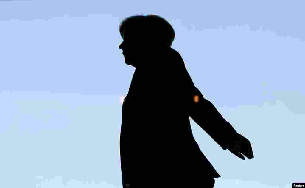 German Chancellor Angela Merkel is silhouetted against the sky as she arrives for a session of the lower house of parliament, the Bundestag, in Berlin on March 20. (Reuters/Fabrizio Bensch)