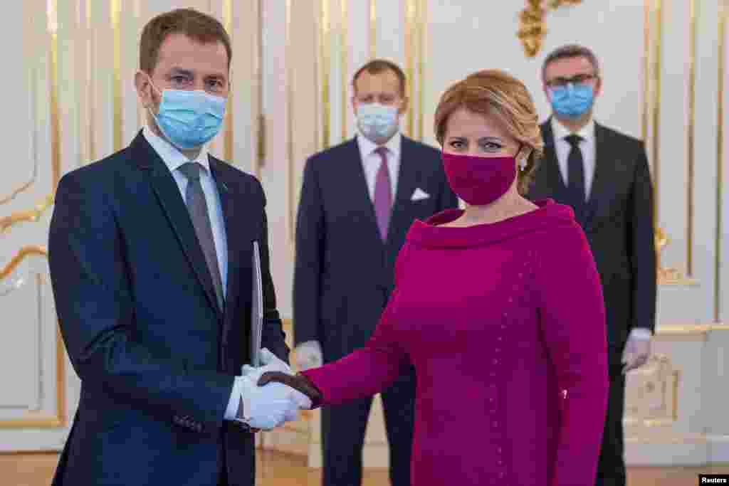 Словашката президентка Зузана Чапутова носи маска в цвят фуксия, съчетана с тоалета ѝ, по време на среща с министър-председателя Игор Матович в деня на встъпването на кабинета му в длъжност на 21 март в Братислава.