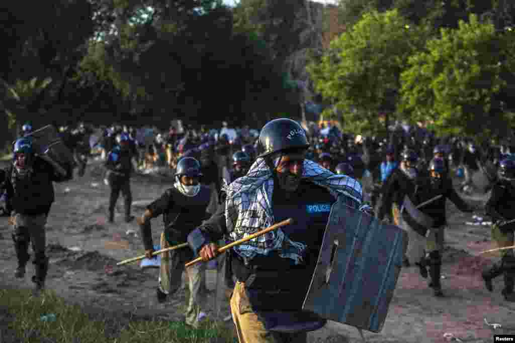 Riot police run away from supporters of Tahir ul-Qadri, a Sufi cleric and leader of the political party Pakistan Awami Tehreek (PAT), during a protest march in Islamabad on August 31. (Reuters/Akhtar Soomro)
