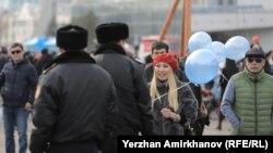 Полицейские направляются к женщине, несущей в руках воздушные шары синего оттенка. Астана, 22 марта 2018 года.