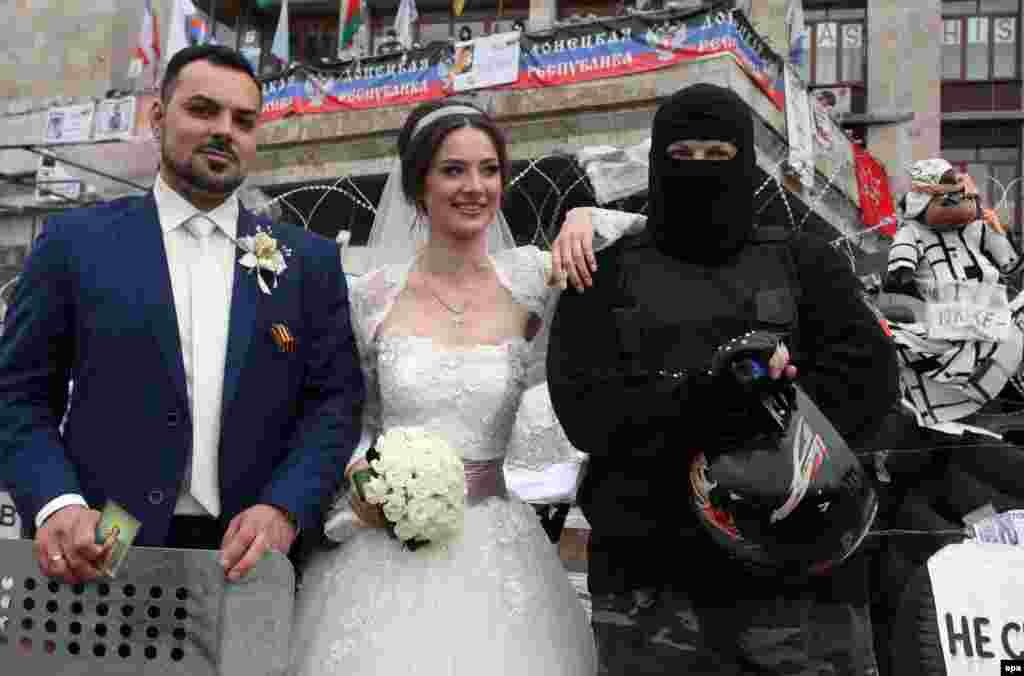 A couple on their wedding day poses with a masked and armed man at the barricades in the center of downtown Donetsk, Ukraine, 02 May 2014.