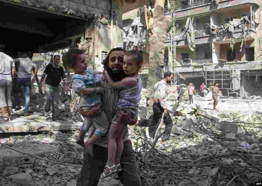 """Бомбы сами не выбирают цели— мужчина несет своих дочерей через развалины в городе Алеппо, который сейчас контролируется группировкой """"Исламское государство"""" и """"Фронтом аль-Нусра"""". 17 сентября 2015 года."""