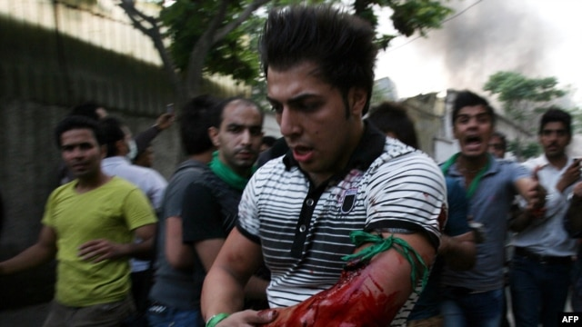 Iranians react as a protestor is wounded at the opposition rally in Tehran on June 15