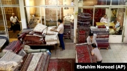 Iranian merchants conduct their business at a carpet market in the old main bazaar in Tehran, Iran, July 23, 2018.