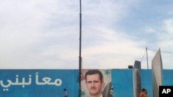 A motorcyclist passes in front of a picture of Syrian President Bashar al-Assad in Damascus in late May.