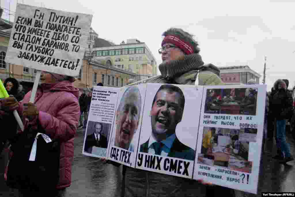 """Where there's sin, they laugh"" alongside images on Vladimir Putin and Dmitry Medvedev."