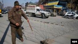 Pamje e një pjesëtari të policisë së Indisë duke vënë pengesë teli