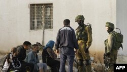 Израильские солдаты разговаривают с жителями палестинской деревни на оккупированной территории (архивное фото)
