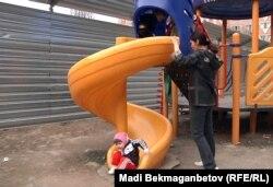 Ақсай-4 ықшам ауданының тұрғыны сырғанақта балаcын ойнатып жүр. Алматы, 7 сәуір 2012 жыл. (Көрнекі сурет)