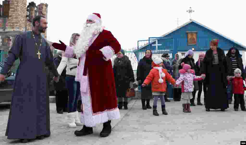 People hold hands during a Christmas celebration after an Orthodox service in the village of Sosnovka, near the Kyrgyz capital, Bishkek.