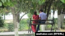 Парень с девушкой сидят на лавочке в Ашхабаде.
