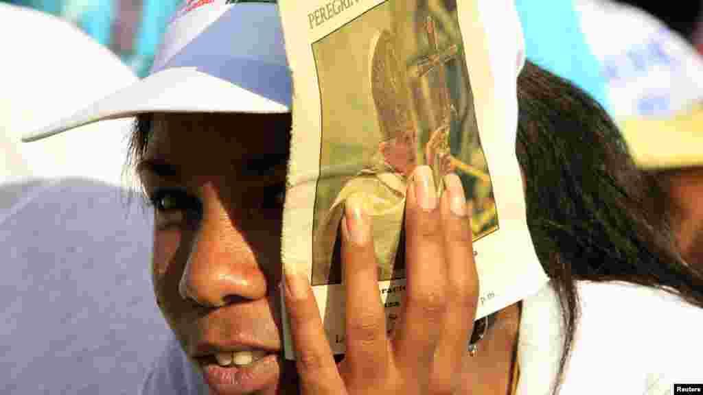 Женщина прикрывает лицо от солнца, ожидая выступления Папы Бенедикта XVI на площади Антонио Масео, Сантьяго-де-Куба