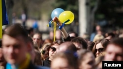 Ukraine -- A woman holds up balloons and ribbons of Ukrainian national colours during a pro-Ukrainian rally in Luhansk, April 17, 2014