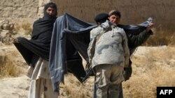 Ооган полициячы Пажвай Алокозай кыштагындагы Мухаммед мечитинде америкалык аскер атып өлтүргөн адамдары эскерген зыяпатка келген жаштарды тинтүүдө. Кандагар провинциясы. 13-март 2012