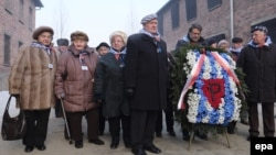 Former prisoners bring candles and flowers to the Death Wall to mark the 72nd anniversary of the liberation of the former Nazi concentration camps at Auschwitz and Birkenau in Oswiecim, Poland, on January 27.