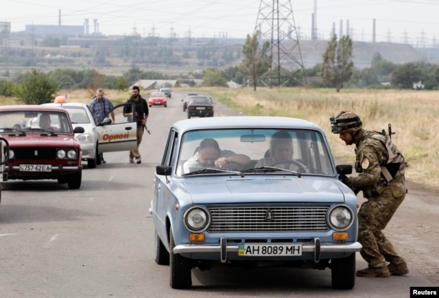 Soldiers from the Ukrainian Azov self-defense battalion check vehicles at a checkpoint in Mariupol. (file photo)