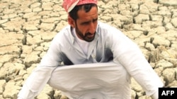 Iraq -- A man squats on dry, cracked earth in the marshes area near the Al-Fuhood village, 01Oct2008
