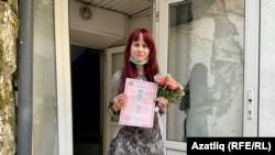 Yelena Gorban shows reporters her wedding certificate on June 23.