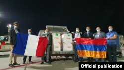 Armenia - Armenian and French officials stand next to the first shipment of coronavirus vaccines donated to Armenia by France, Yerevan, September 14, 2021.
