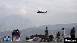 Военен хеликоптер прелита над продавачи на хвърчила в Кабул, Афганистан